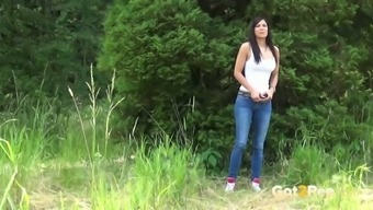 Playful blonde lady in denim Rebecca pees within the wood