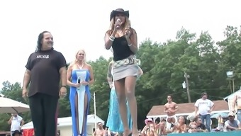 Attractive brown in high heel boots performing arts with the stripper post outside